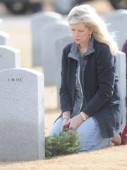 Camille Newman of Abilene sits at the grave of her father, Bertram Jordan Jr., after laying a wreath at his grave. Jordan, who was a master sergeant in the U.S. Army and served in Korea, died last year at age 86. Newman was participating in a wreath-laying ceremony at the Texas State Veterans Cemetery on Saturday, Dec. 17, 2016 in Abilene.