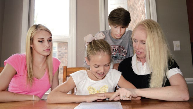 Sandi Martin goes over her current chore chart with her daughters Audry and Mackenzie and son, Porter.