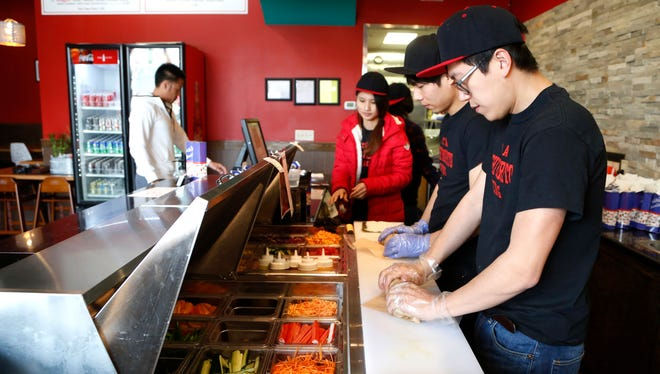 Kyle Zhuo, right, and Jean Lin prepare rolls Monday, March 28, 2016, at Sushi Burrito, 350 E. State Street in Wabash Landing.