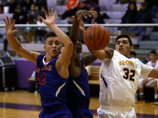 Los Lunas' Zanen Zeller, left, and Thean Nelson fight for the lose ball against Kirtland Central's Noah Lee on Tuesday at Bronco Arena in Kirtland.
