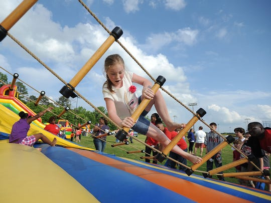 Kennedy Manning, 9, braces for a fall as she is unable to keep her balance on a rope ladder bridge in a kids' area at the Flowood Family Festival at Liberty Park in Flowood in 2013.