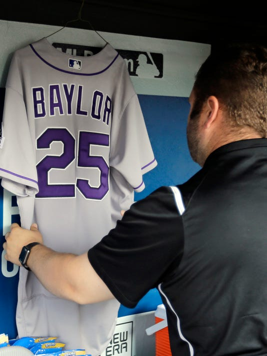 Colorado Rockies equipment manager Mike Pontarelli hangs former Rockies manager Don Baylor's jersey in the dugout before the Rockies play the Cleveland Indians in a baseball game, Tuesday, Aug. 8, 2017, in Cleveland. Baylor died Monday of cancer. (AP Photo/Tony Dejak)