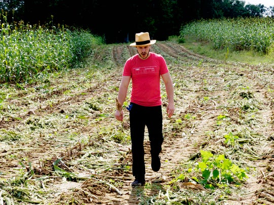 Palmer Mason, cocktail caterer at Craft Accommodations, walks through a sorghum field at Muddy Pond Sorghum Mill outside of Monterey, Tennessee, on Monday, September 18, 2017.