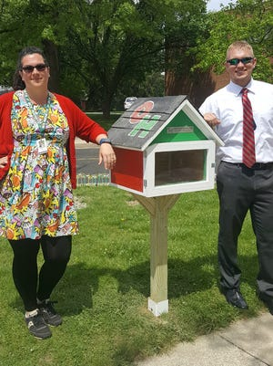 Art teacher Mackenzie Warren and FFA member Peyton Salyers stand with a new Little Free Library.