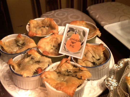 At a pie party, individual pot pies are topped with puff pastry and thyme sprigs.