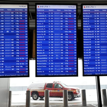 A departure board at New York LaGuardia shows cancelled flights with a fire vehicle in the background after Delta Flight 1086 from Atlanta skidded off a runway while landing.