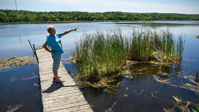 Barb Platten talks Thursday, July 5, about an upcoming project to remove many large floating bogs that cover large areas of Linneman Lake near Avon.