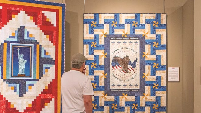 "Carlos Mendez of Bowling Green, Ky.,  looks at a quilt titled ""Home of the Brave"" Friday, Aug. 28, 2015 at the National Quilt Museum in downtown Paducah. The quilt is one of 34 patriotically themed pieces on display as part of an exhibit brought to the museum by the Quilts of Valor Foundation."