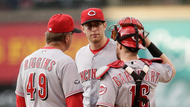 Reds pitching coach Mark Riggins and catcher Tucker Barnhart talk with starting pitcher Jon Moscot in the first inning against the Colorado Rockies at Coors Field.