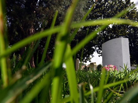 The gravesite of Mississippi writer Eudora Welty is seen as grass grows tall at Greenwood Cemetery Wednesday.