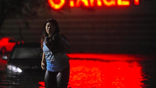 Rosie Kue, 17, of Sioux Falls, wades through high water at the intersection of 43rd Street and Kelley Avenue near the Louise Avenue Target store after meeting her sister, Nue Kue, 27, who works at Kohl's after heavy rains Thursday, Aug. 27, 2015, in Sioux Falls.