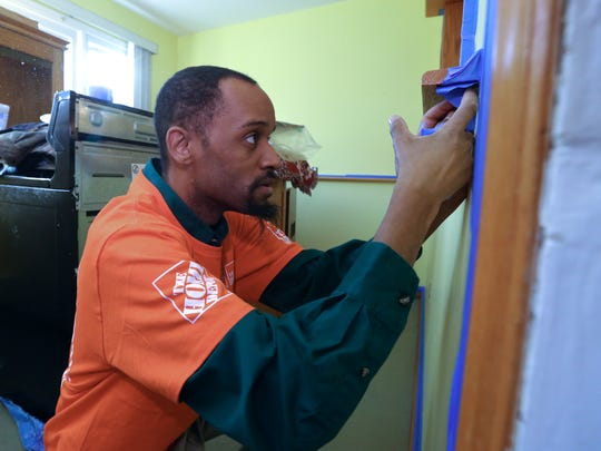 Rasheed Nuri of Home Depot puts down painter's tape at Richard Gaglione's Congers home Jan. 3, 2018.