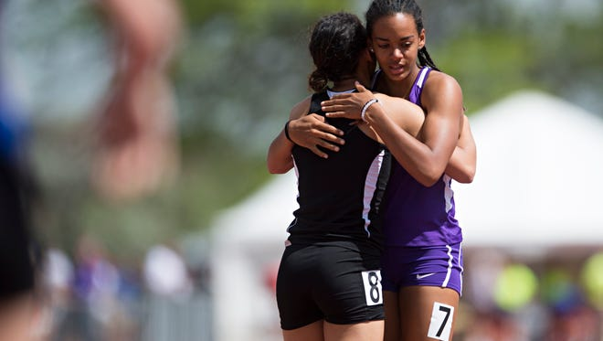 Audra Koopman of Fort Collins High School gets a hug after finishing the 5A girls 100-meter dash during the Colorado state track and field championships at Jefferson County Stadium in Lakewood on Saturday.