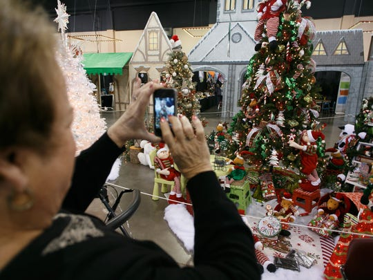 Ann Everett snaps a picture of a Christmas tree at the 2014 Jubilee of Trees at the Dixie Center in St. George.