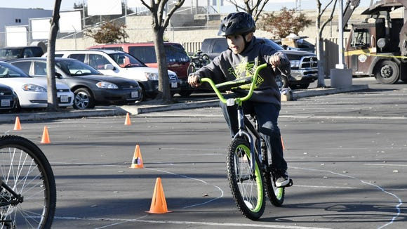 A bike recipient rides through an obstacle course in the parking lot of Tulare County Sheriff's Department new location Wednesday morning.