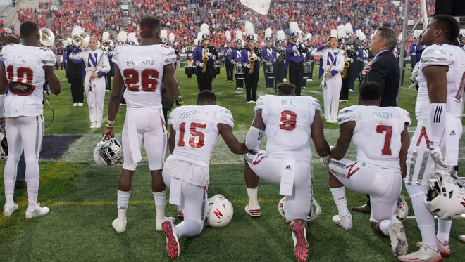 Nebraska linebacker Michael Rose-Ivey (15), defensive end DaiShon Neal (9) and linebacker Mohamed Barry (7) kneel during the national anthem before the team's game against Northwestern in Evanston, Ill., on Saturday, Sept. 24, 2016. Rose-Ivey said Monday he and his family have received racially charged criticism on social media, and said the responses show why the protest is necessary.