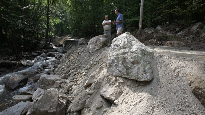 Philipstown Highway Department Superintendent Roger Chirico, left, and town Supervisor Richard Shea stand Sept. 1, 2011, on East Mountain Road South, which was washed out by Tropical Storm Irene.