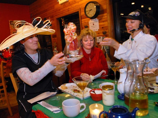 Chef and baker Anita Kern, right, of st. Clair Township smiles after presenting Trisha Schweiger, left, of St. Clair with her prize for best hat while seated with Jean Laurain, of Casco Township at the demonstration table, Tuesday December 20, 2011, during a Christmas tea inside Sue's Coffee House in St. Clair.