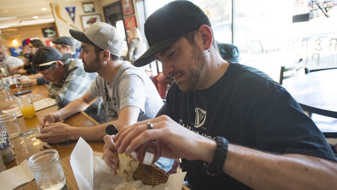 Dillon DeJesus applies hot sauce to his sandwich during the lunch rush at the Pickle Barrel on Wednesday, Feb. 14, 2018. The iconic Laurel Street sandwich shop is celebrating its 30th year.