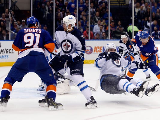 Winnipeg Jets right wing Blake Wheeler (26) goes airborne as New York Islanders center Mikhail Grabovski (84) of Germany scores a goal in the second period of an NHL hockey game in Uniondale, N.Y., Tuesday, Oct. 28, 2014. New York Islanders center John Tavares (91) defends. (AP Photo/Kathy Willens)