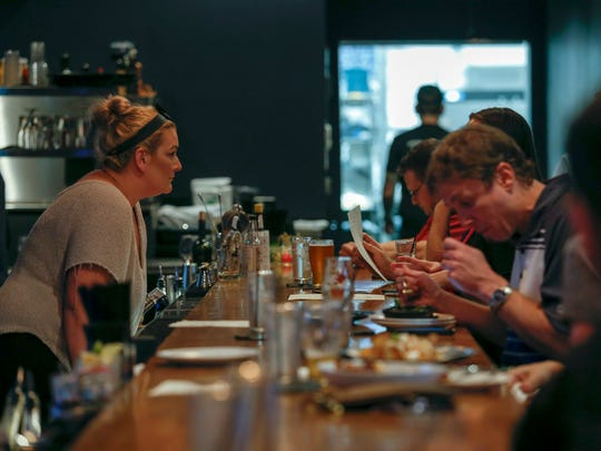 Jessica Lundgren, of Pleasant Ridge, and a bartender for Berkley Common, takes an order from a customer on Tuesday, Oct. 3, 2017 in Berkley. Berkley Common recently opened their doors and is located on 12 Mile Rd. and Griffith Ave. in Berkley.