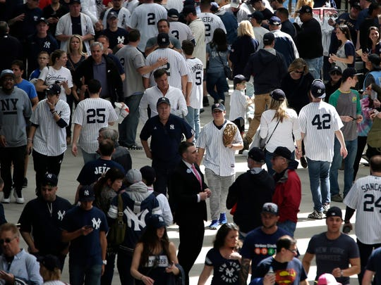 Baseball fans walk through Yankee Stadium before a baseball game between the New York Yankees and the Tampa Bay Rays, Monday, April 10, 2017, in New York. (AP Photo/Seth Wenig)