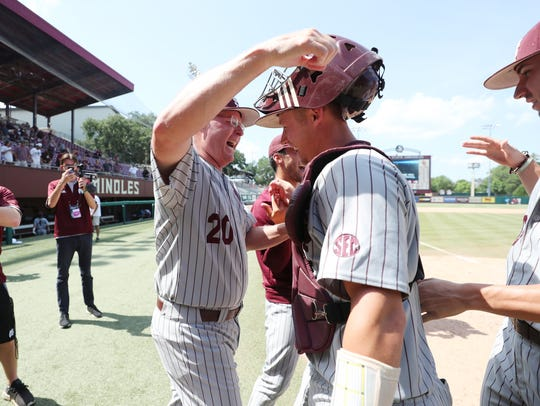 Mississippi State coach Gary Henderson hugs catcher