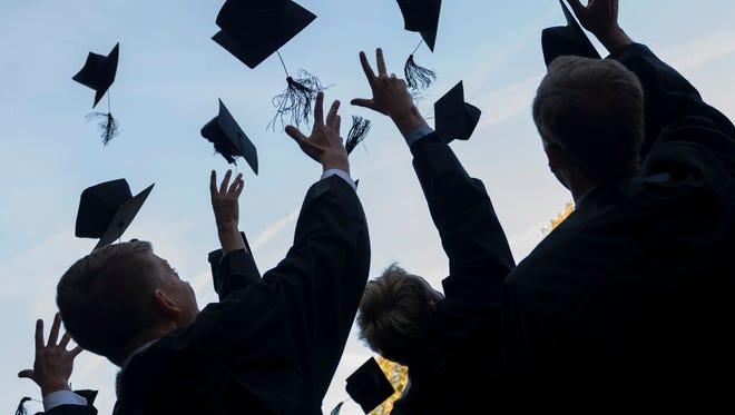 Graduates toss their caps.