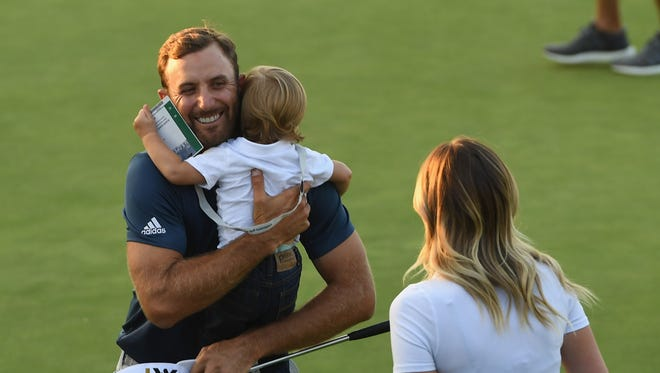 Dustin Johnson celebrates his triumph with wife Paulina Gretzky and son Tatum.
