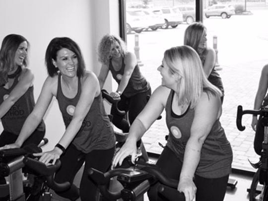 Stephanie Breaux Bradley and her instructors laugh during a cycle class.