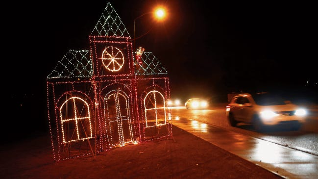 Motorists drive by a holiday display during the Aztec Sparkles event last year near the Aztec Urgent Care  in Aztec.
