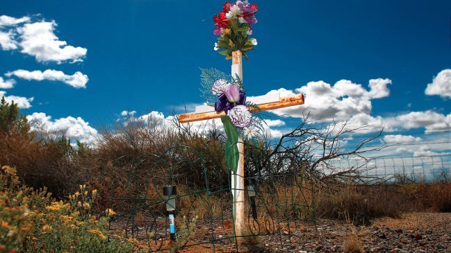 A decorated cross is seen in this file photo near mile marker 130 south of Bloomfield on U.S. Highway 550. It marks the area where a family of four was killed in a crash in a southbound lane.