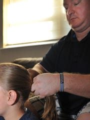 Doug Marquardt, right, puts his daughter's hair, Adalyn,8, into a ponytail before styling her hair. Marquardt says he started learning how to style and cut Adalyn's hair when she was four-years-old.