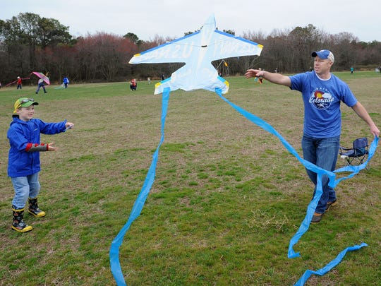 Todd Lawson, of Harbeson, helps his son Cooper, 7 get their kite to fly at the 48th Great Delaware Kite Festival Friday.