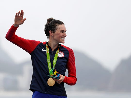 Gwen Jorgensen, of the United States, waves after receiving the gold medal for winning the women's triathlon event on Copacabana beach at the 2016 Summer Olympics in Rio de Janeiro, Brazil, Saturday, Aug. 20, 2016. (AP Photo/David Goldman) ORG XMIT: OGOL121