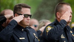 Wetumpka police officers salute during the playing
