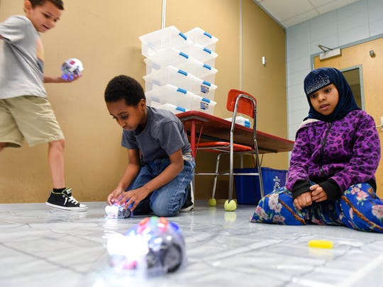 Second-graders Aden Khan, Mohamed Abdi and Najma Hussein program their Blue-Bot robots to go through a course Thursday, Sept. 14, at Talahi Community School.