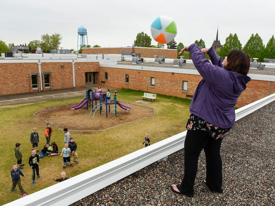 Principal Sue Paasch throws a beach ball off the roof