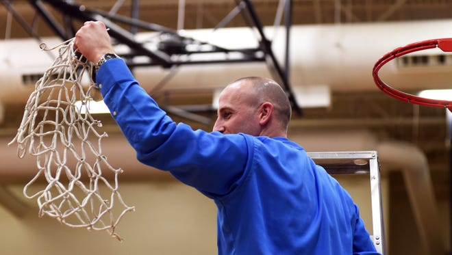 Philo coach Greg Haberfield holds up the net after the Electrics earned a 49-40 win against West Holmes in a Division II sectional final on Saturday at The Power Plant.