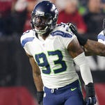Dec 21, 2014; Glendale, AZ, USA; Seattle Seahawks outside linebacker Bruce Irvin (51) and Seattle Seahawks defensive end O'Brien Schofield (93) celebrate against the Arizona Cardinals during the first half at University of Phoenix Stadium.