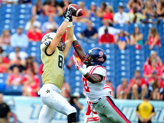 Ole Miss' A.J. Moore, right, breaks up a pass intended for Vanderbilt's Kris Kentera during the third quarter Saturday.