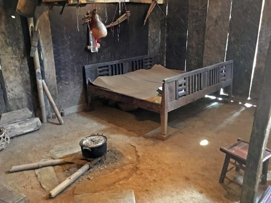 This is a ground-level Hmong house of wide wooden planks