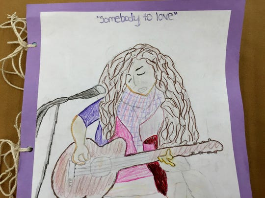 "Since learning that singer-songwriter Valerie June would be paired with their school, Lancaster Elementary students studied her life and music and then bound their sketches and writing in a book. The cover is a student drawing of June singing one of her songs, ""Somebody to Love."""