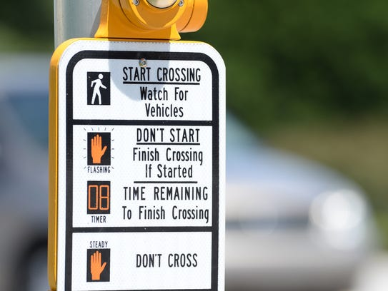 A crossing sign at the intersection of White Horse Road and Lilly Street in Greenville.
