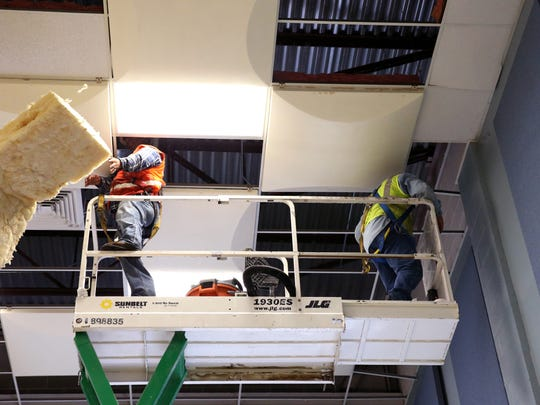 Rudy Sosa (left) and Jose Luis, with Port Enterprise, remove work on demolition of damaged roof acoustic tiles from the Carroll High School band hall Friday, September 1, 2017. The hall was damaged by water during Hurricane Harvey.