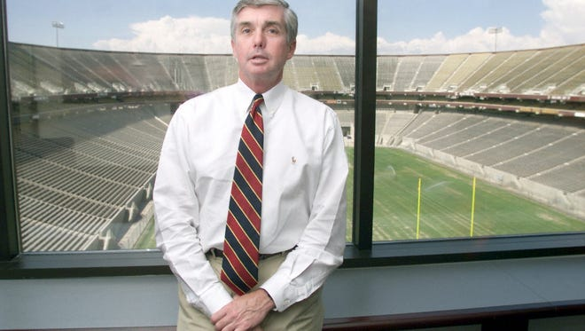 In this file photo from July 21, 1999, Arizona State University Athletic Director Kevin White poses in his office with Sun Devil Stadium in the background.