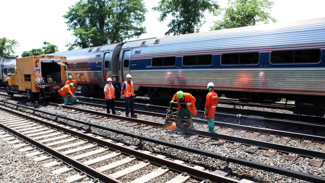 A train passes as Metro-North employees finish pot welding a rail near the Hastings-on-Hudson station on July 9, 2014.