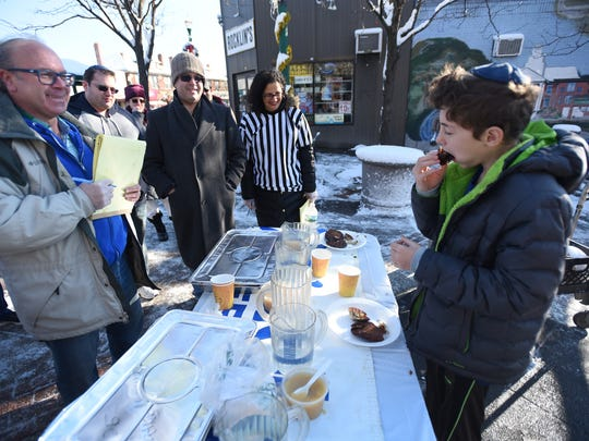 Stuart Kahan, left, chef and co-owner of Ma'adan Catering, looks as Billy Mallinholtz, 12, of Teaneck competes by eating three latkes in three minutes during the latke-eating competition in Teaneck on Sunday.