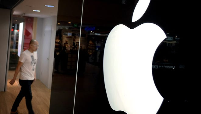 A man walks into one of Apple's authorised premium resellers' outlets on Monday, Nov. 16, 2015, in Singapore. Apple will open its first retail store in Singapore, which will also be Southeast Asia's first to be powered solely by solar energy, officials said Monday. (AP Photo/Wong Maye-E) ORG XMIT: SIN101