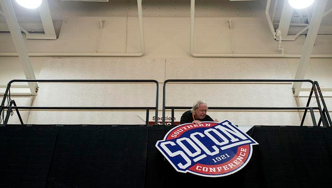 A worker hangs a sign as preparations are underway for the Southern Conference Basketball Championships Wednesday at the U.S. Cellular Center in downtown Asheville. Games begin Thursday and will continue through Monday.